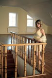 Το νέο κορίτσι βάσισε στο χαρασμένο ξύλινο κιγκλίδωμα Στοκ Εικόνες
