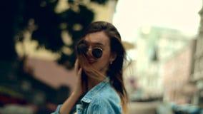 Το νέο κορίτσι γοητείας με τα κόκκινα χείλια περπατά γύρω από την οδό και τις στροφές στη κάμερα φιλμ μικρού μήκους