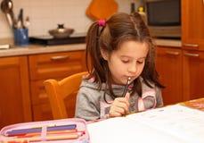 Το νέο κορίτσι γράφει με το μολύβι στο σχολικό βιβλίο Στοκ φωτογραφία με δικαίωμα ελεύθερης χρήσης