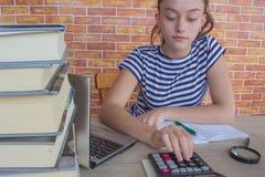 Το νέο κορίτσι γράφει στο σημειωματάριο μεταξύ των βιβλίων Κορίτσι που εργάζεται στην εργασία του νέο ελκυστικό κορίτσι σπουδαστώ Στοκ Εικόνες