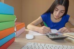 Το νέο κορίτσι γράφει στο σημειωματάριο μεταξύ των βιβλίων Κορίτσι που εργάζεται στην εργασία του νέο ελκυστικό κορίτσι σπουδαστώ Στοκ Εικόνα