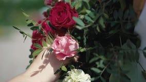 Το νέο κορίτσι διακοσμεί με την αψίδα λουλουδιών πριν από το γάμο των newlyweds απόθεμα βίντεο