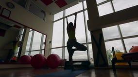 Το νέο κορίτσι εκτελεί τα asanas Vrikshasana στη γυμναστική σκοτεινό πλαίσιο φιλμ μικρού μήκους