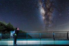 Το νέο κορίτσι εξετάζει επάνω το νυχτερινό ουρανό και το γαλακτώδη γαλαξία τρόπων με διοφθαλμικό στοκ φωτογραφία