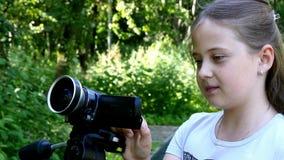 Το νέο κορίτσι εξετάζει τα βιντεοκάμερα στο υπόβαθρο του πράσινου υποβάθρου πάρκων φιλμ μικρού μήκους