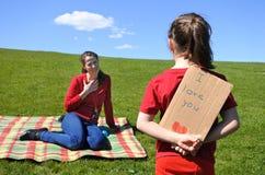 Το νέο κορίτσι εξετάζει τη μητέρα της και κρατά πίσω από την την πλάτη μια κάρτα στοκ φωτογραφία