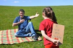 Το νέο κορίτσι εξετάζει τον πατέρα της και κρατά πίσω από την την πλάτη μια κάρτα στοκ εικόνες με δικαίωμα ελεύθερης χρήσης