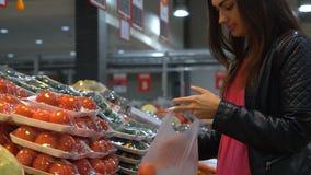 Το νέο κορίτσι επιλέγει τα λαχανικά στην υπεραγορά φιλμ μικρού μήκους