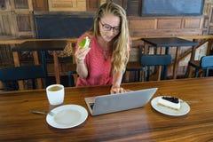Το νέο κορίτσι εργάζεται στον υπολογιστή και το κέικ, τρόφιμα στον υπολογιστή, μια κακή συνήθεια τρώει Στοκ εικόνα με δικαίωμα ελεύθερης χρήσης