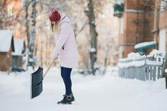 Το νέο κορίτσι εφήβων καθαρίζει το χιόνι κοντά στο σπίτι, κρατώντας ένα φτυάρι και ένα κουπί ξοδεψτε το χρόνο Στοκ Εικόνα