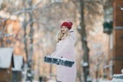Το νέο κορίτσι εφήβων καθαρίζει το χιόνι κοντά στο σπίτι, κρατώντας ένα φτυάρι και ένα κουπί ξοδεψτε το χρόνο Στοκ φωτογραφία με δικαίωμα ελεύθερης χρήσης
