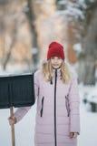 Το νέο κορίτσι εφήβων καθαρίζει το χιόνι κοντά στο σπίτι, κρατώντας ένα φτυάρι και ένα κουπί ξοδεψτε το χρόνο Στοκ Φωτογραφία