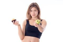 Το νέο κορίτσι ικανότητας τεντώνει εμπρός το χέρι του με τη Apple και ένα δευτερόλεπτο κρατά το fruitcake Στοκ Φωτογραφίες