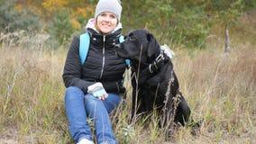 Το νέο κορίτσι κάθεται σε μια χλόη με ένα μεγάλο σκυλί φωτογραφία στοκ φωτογραφία με δικαίωμα ελεύθερης χρήσης