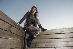 Το νέο κορίτσι κάθεται στο φράκτη Στοκ εικόνες με δικαίωμα ελεύθερης χρήσης