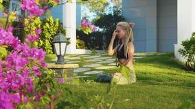 Το νέο κορίτσι κάθεται στο χορτοτάπητα και να κάνει την πρακτική αναπνοής γιόγκας pranayama απόθεμα βίντεο