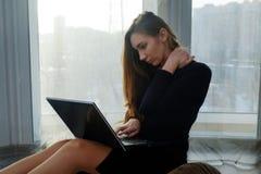 Το νέο κορίτσι κάθεται την εργασία με ένα lap-top Στοκ Φωτογραφία