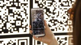 Το νέο κορίτσι κοντά στον τοίχο με έναν κώδικα QR χρησιμοποιεί ένα τηλέφωνο και παίρνει μια φωτογραφία απόθεμα βίντεο