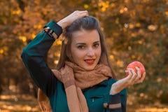 Το νέο κορίτσι κρατά ένα χέρι στην τρίχα ενώ άλλο κρατά την κινηματογράφηση σε πρώτο πλάνο της Apple Στοκ φωτογραφία με δικαίωμα ελεύθερης χρήσης