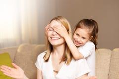 Το νέο κορίτσι κλείνει τα μάτια μητέρων της Η όμορφες μητέρα και λίγη κόρη χαμογελούν στοκ εικόνες