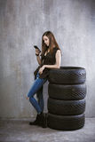 Το νέο κορίτσι με ένα κινητό τηλέφωνο, κλίνει ενάντια στις ρόδες επάνω Στοκ Εικόνες