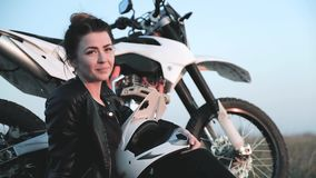 Το νέο κορίτσι με ένα κράνος μοτοσικλετών στα χέρια της απολαμβάνει το ηλιοβασίλεμα κοντά στη μοτοσικλέτα της απόθεμα βίντεο