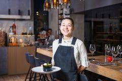 Το νέο κορίτσι με ένα όμορφο χαμόγελο ένας σερβιτόρος κρατά στα χέρια της ένα γλυκό πιάτο επιδορπίων διαταγής της ιταλικής κουζίν Στοκ Φωτογραφία