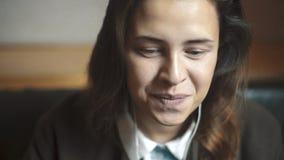 Το νέο κορίτσι με μακρυμάλλη ακούει τη μουσική μέσω των ακουστικών απόθεμα βίντεο