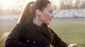 Το νέο κορίτσι με τα ασύρματα ακουστικά στα αυτιά εκτελεί τις ασκήσεις ικανότητας μια ηλιόλουστη ημέρα φθινοπώρου απόθεμα βίντεο