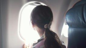 Το νέο κορίτσι με τα γυαλιά εξετάζει με το ενδιαφέρον το παράθυρο ενός βίντεο μήκους σε πόδηα αποθεμάτων αεροπλάνων απόθεμα βίντεο