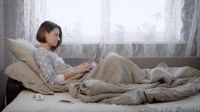 Το νέο κορίτσι με την καφετιά τρίχα, που ντύθηκε σε ένα γκρίζο πουλόβερ, που κάθεται στο κρεβάτι, κάτω από ένα κάλυμμα επάνω σε έ απόθεμα βίντεο