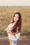 Το νέο κορίτσι με τη μακριά καφετιά τρίχα κρατά μια δέσμη των αυτιών διαθέσιμων Στοκ Εικόνες
