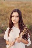 Το νέο κορίτσι με τη μακριά καφετιά τρίχα κρατά μια δέσμη των αυτιών διαθέσιμων Στοκ φωτογραφίες με δικαίωμα ελεύθερης χρήσης