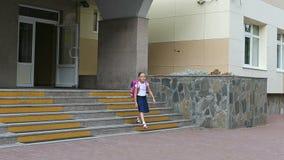 Το νέο κορίτσι με το σακίδιο πλάτης βγαίνει από το σχολείο κάτω Ένα κορίτσι στη σχολική στολή βγαίνει από το σχολείο και κατεβαίν Στοκ εικόνες με δικαίωμα ελεύθερης χρήσης