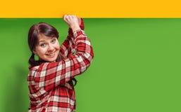 Το νέο κορίτσι με το χαμόγελο κρατά το έμβλημα διαφήμισης στοκ φωτογραφία με δικαίωμα ελεύθερης χρήσης