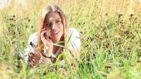 Το νέο κορίτσι μιλά στο τηλέφωνο στο πάρκο πόλεων φιλμ μικρού μήκους