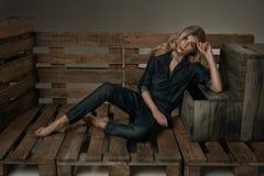 Το νέο κορίτσι μόδας με τα όμορφα μακριά ξανθά μαλλιά που βρίσκονται επιζητά Στοκ φωτογραφία με δικαίωμα ελεύθερης χρήσης