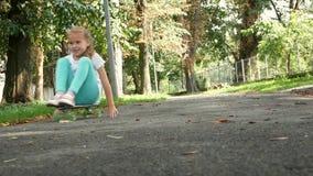 Το νέο κορίτσι οδηγά skateboard σε μια καθισμένη θέση στο πάρκο κίνηση αργή φιλμ μικρού μήκους