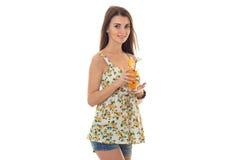 Το νέο κορίτσι ομορφιάς στα σορτς τζιν και sarafan με το floral σχέδιο πίνει το πορτοκαλί κοκτέιλ και την εξέταση τη κάμερα Στοκ Εικόνες