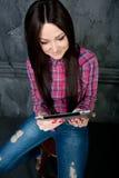 Το νέο κορίτσι ονειρεύεται και κρατά το touchpad Στοκ φωτογραφία με δικαίωμα ελεύθερης χρήσης