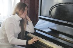 Το νέο κορίτσι παίζει το πιάνο - καταθλιπτική έννοια στοκ φωτογραφία