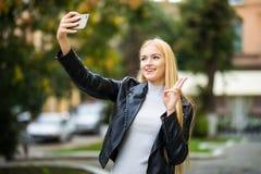 Το νέο κορίτσι παίρνει selfie από τα χέρια με το τηλέφωνο στην οδό θερινών πόλεων Αστική έννοια ζωής Στοκ Φωτογραφία