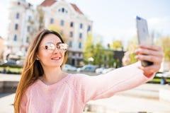 Το νέο κορίτσι παίρνει selfie από τα χέρια με το τηλέφωνο στην οδό θερινών πόλεων Αστική έννοια ζωής Στοκ φωτογραφίες με δικαίωμα ελεύθερης χρήσης