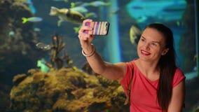 Το νέο κορίτσι παίρνει Selfie Το ενυδρείο με τα ψάρια είναι στο υπόβαθρο Είναι πολύ ευτυχής και εύθυμη και έχοντας την πολλή απόθεμα βίντεο