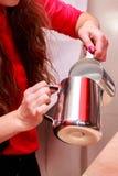 Το νέο κορίτσι παρασκευάζει τον καφέ στοκ φωτογραφία