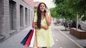 Το νέο κορίτσι περπατά γύρω από την πόλη μετά από να ψωνίσει και να μιλήσει στο τηλέφωνο 4K απόθεμα βίντεο