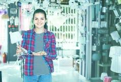 Το νέο κορίτσι πελατών στο ελαφρύτερο κατάστημα επιλέγει μοντέρνο και τον τρόπο Στοκ Φωτογραφία