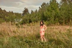 Το νέο κορίτσι πηγαίνει μέσω της ψηλής χλόης σε έναν τομέα ελών Στοκ φωτογραφία με δικαίωμα ελεύθερης χρήσης
