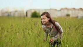Το νέο κορίτσι πηγαίνει στη βαθιά χλόη απόθεμα βίντεο