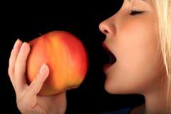 Το νέο κορίτσι που δαγκώνει τη μεγάλη Apple, γυναίκα τρώει το μήλο, υγιής κατανάλωση Στοκ Εικόνες